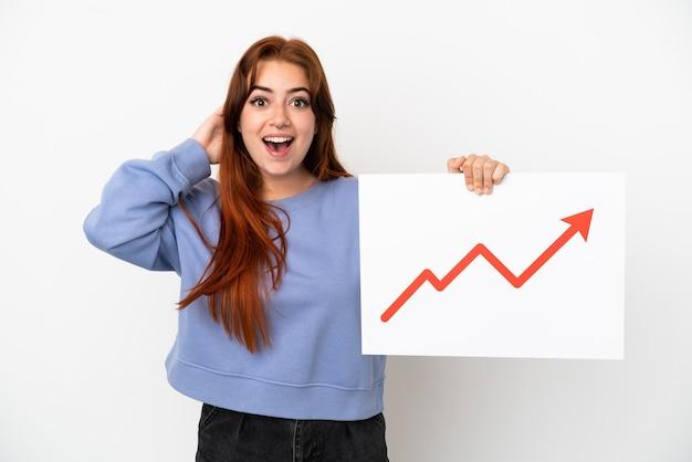 Mulher jovem ruiva isolada no fundo branco segurando uma placa com um símbolo de seta de estatísticas crescentes com expressão de surpresa