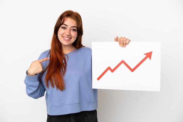 Mulher jovem ruiva isolada no fundo branco segurando uma placa com um símbolo de seta de estatísticas crescentes e apontando-a
