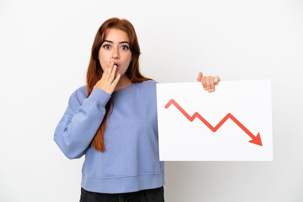 Mulher jovem ruiva isolada no fundo branco segurando uma placa com um símbolo de seta decrescente de estatísticas com expressão de surpresa