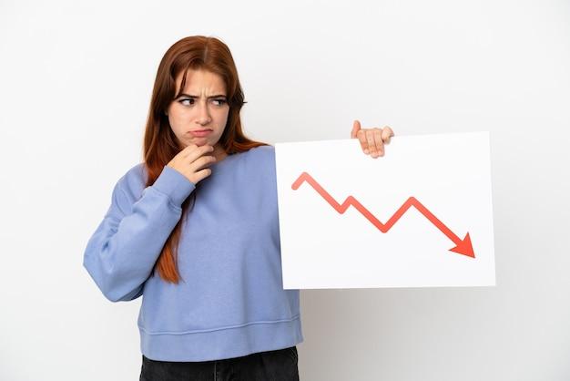 Mulher jovem ruiva isolada no fundo branco segurando uma placa com um símbolo de seta decrescente de estatísticas e pensando