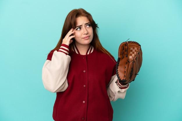 Mulher jovem ruiva jogando beisebol isolado em um fundo azul, tendo dúvidas e pensando