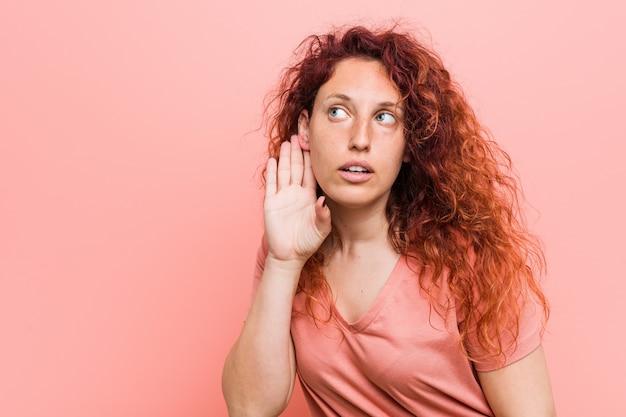 Mulher jovem ruiva natural e autêntica, tentando ouvir uma fofoca.