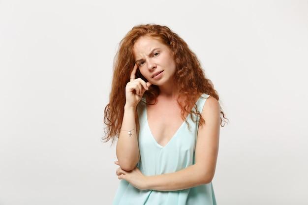 Mulher jovem ruiva pensativa perplexa em roupas leves casuais posando isolado no fundo branco, retrato de estúdio. conceito de estilo de vida de emoções sinceras de pessoas. simule o espaço da cópia. colocando a mão na cabeça.