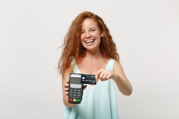 Mulher jovem ruiva rindo posando isolado no fundo branco. conceito de estilo de vida de pessoas. simule o espaço da cópia. segurando um terminal de pagamento bancário moderno sem fio para processar, adquirir pagamentos com cartão de crédito.