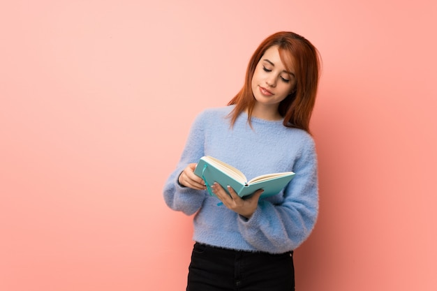 Mulher jovem ruiva rosa segurando um livro e gostar de ler