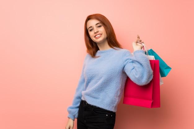 Mulher jovem ruiva rosa segurando um monte de sacos de compras