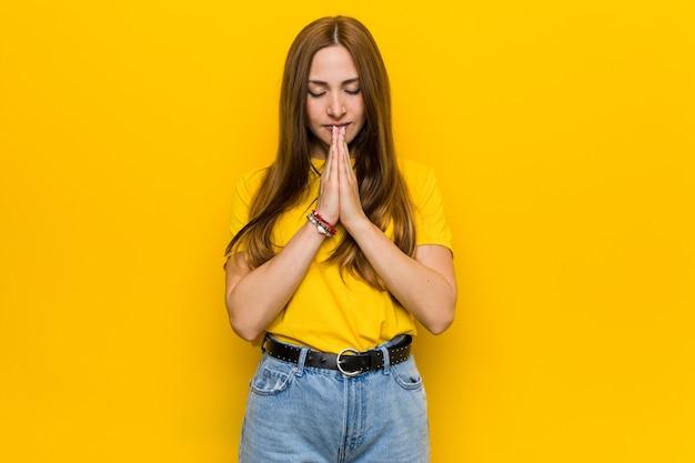 Mulher jovem ruiva ruiva de mãos dadas orando perto da boca, sente-se confiante.