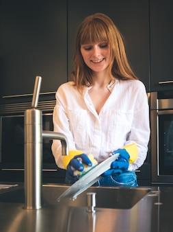Mulher jovem ruiva russa esfregando com um grande sorriso em uma cozinha moderna