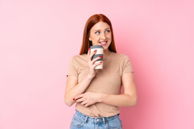 Mulher jovem ruiva segurando café para levar