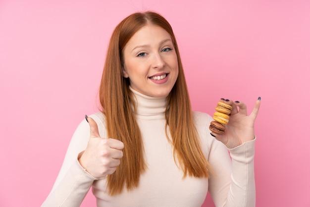 Mulher jovem ruiva segurando macarons franceses coloridos com polegares para cima
