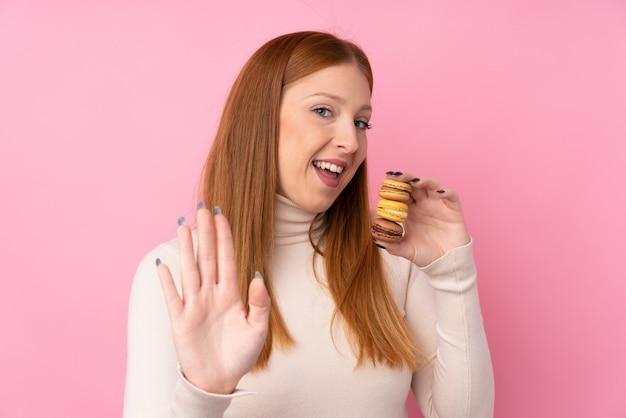 Mulher jovem ruiva segurando macarons franceses coloridos e saudação