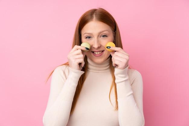 Mulher jovem ruiva segurando macarons franceses coloridos e sorrindo
