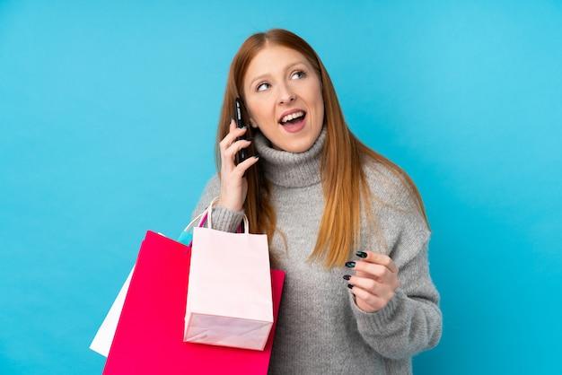 Mulher jovem ruiva segurando sacolas de compras e chamando um amigo com seu telefone celular