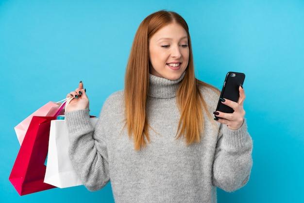 Mulher jovem ruiva segurando sacolas de compras e escrever uma mensagem com o celular para um amigo