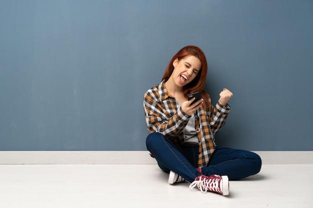 Mulher jovem ruiva sentada no chão com o telefone em posição de vitória