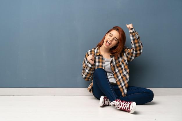 Mulher jovem ruiva sentada no chão comemorando uma vitória