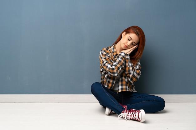 Mulher jovem ruiva sentada no chão fazendo gesto de sono na expressão dorable