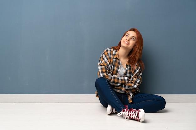 Mulher jovem ruiva sentada no chão, olhando para cima, enquanto sorrindo