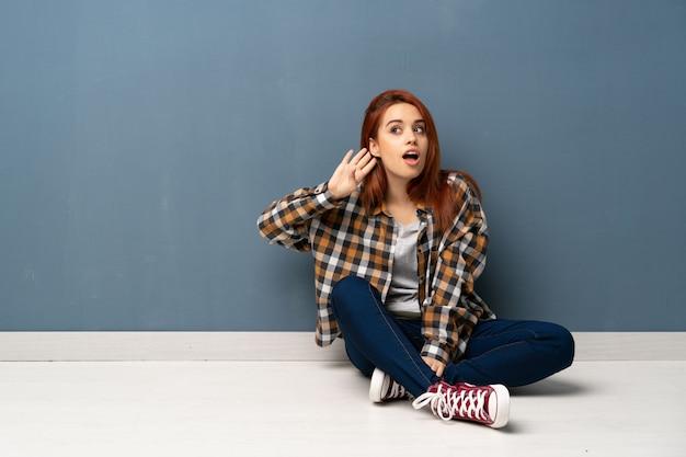 Mulher jovem ruiva sentada no chão ouvindo algo, colocando a mão sobre a orelha