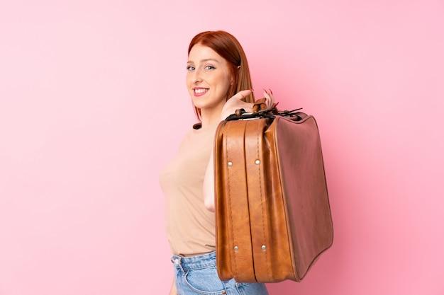 Mulher jovem ruiva sobre fundo rosa isolado, segurando uma mala vintage