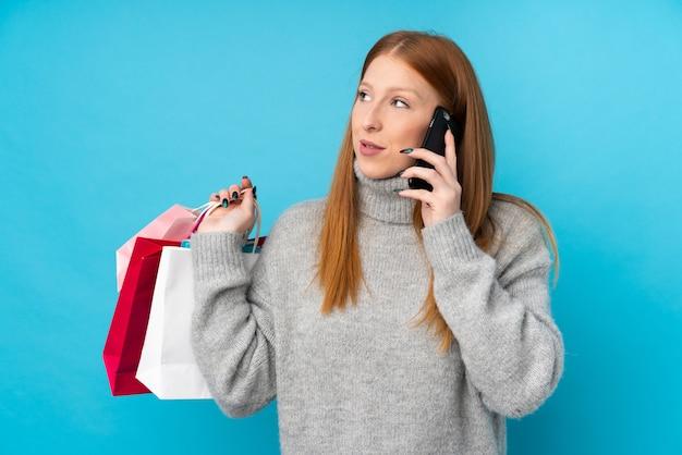 Mulher jovem ruiva sobre parede azul isolada segurando sacolas de compras e chamando um amigo com seu telefone celular