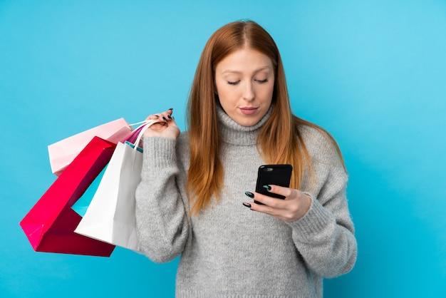 Mulher jovem ruiva sobre parede azul isolada segurando sacolas de compras e escrever uma mensagem com o celular para um amigo