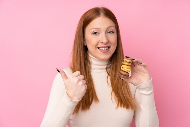 Mulher jovem ruiva sobre parede rosa isolada segurando macarons franceses coloridos e apontando o lado