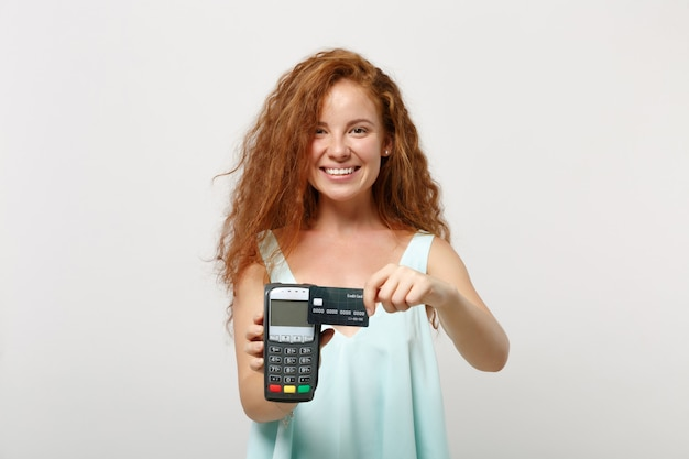 Mulher jovem ruiva sorridente posando isolado no fundo branco. conceito de estilo de vida de pessoas. simule o espaço da cópia. segurando um terminal de pagamento bancário moderno sem fio para processar, adquirir pagamentos com cartão de crédito.