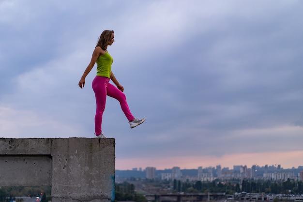 Mulher jovem saindo da borda do edifício sobre o dramático pôr do sol e o conceito de plano de fundo da paisagem urbana de suicídio e desespero