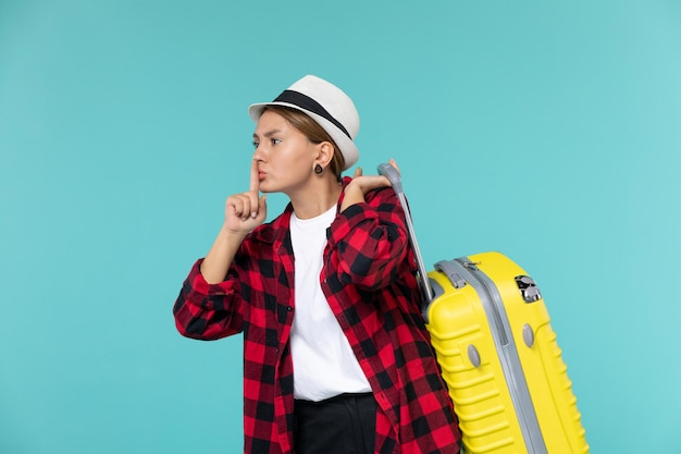 Mulher jovem saindo de férias com sua bolsa amarela na mesa azul