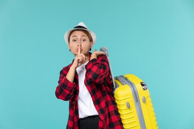 Mulher jovem saindo de férias com sua bolsa amarela no espaço azul claro