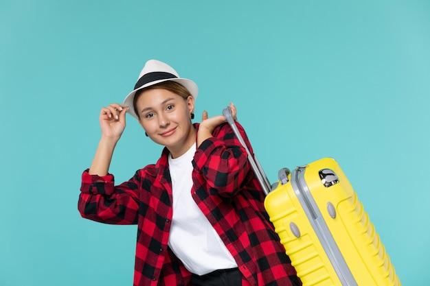 Mulher jovem saindo de férias com sua bolsa amarela no espaço azul