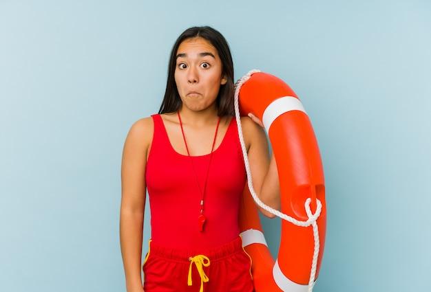 Mulher jovem salva-vidas encolhe os ombros e abre os olhos confusos.
