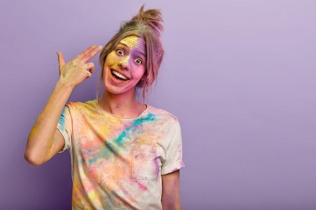 Mulher jovem satisfeita e alegre atira no templo, demonstra gesto de arma com o dedo, sinal de suicídio, inclina a cabeça, tem uma camiseta colorida e o rosto manchado de pó no feriado de holi, espaço em branco à parte para texto