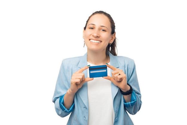 Mulher jovem satisfeita está segurando seu querido cartão de crédito.
