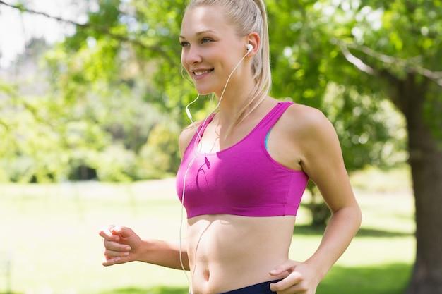 Mulher jovem saudável e bonita no sutiã esportivo, movimentando-se no parque