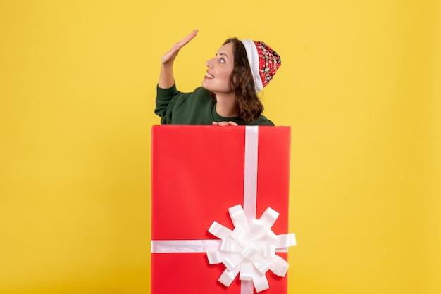 Mulher jovem se escondendo dentro de uma caixa de presente na mesa amarela, mulher jovem, vista frontal, cor, emoção, ano novo