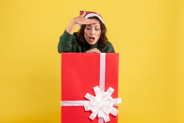 Mulher jovem se escondendo dentro de uma caixa de presente no chão amarelo mulher jovem, vista frontal, cor, emoção, ano novo