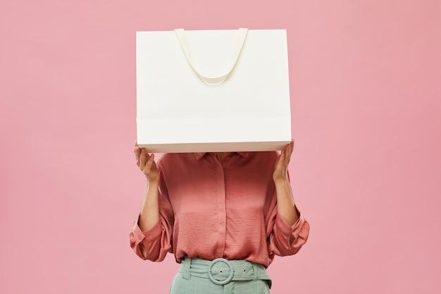 Mulher jovem se escondendo diante de uma grande sacola de compras branca em pé contra o fundo rosa
