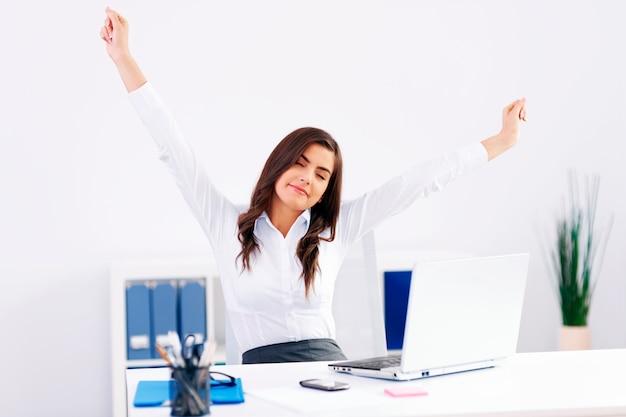 Mulher jovem se espreguiçando no escritório