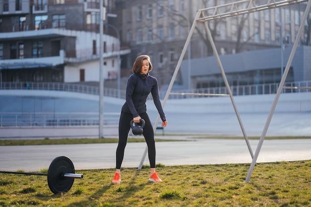 Mulher jovem se exercitando com um kettlebell do lado de fora no estádio