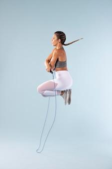 Mulher jovem se exercitando com uma corda de pular