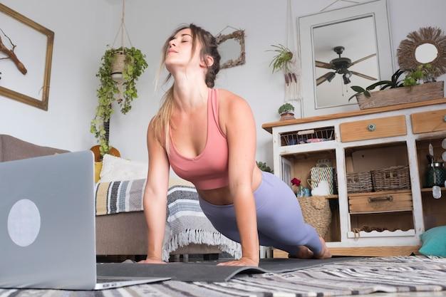 Mulher jovem se exercitando em casa fazendo flexões e olhando para seu laptop pessoal para aprender ou ensinar o conceito de pessoas de estilo de vida saudável grátis.