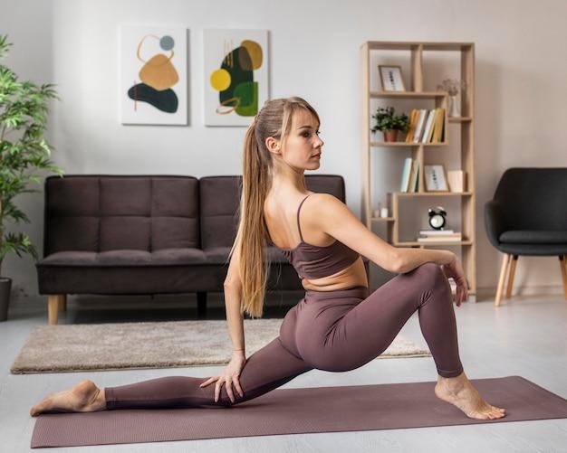 Mulher jovem se exercitando em casa no tatame