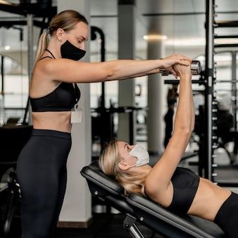 Mulher jovem se exercitando na academia e usando máscara