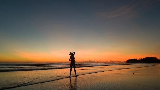 Mulher jovem se exercitando na praia ao pôr do sol