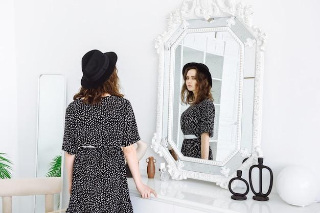 Mulher jovem se olhando no espelho em uma sala iluminada