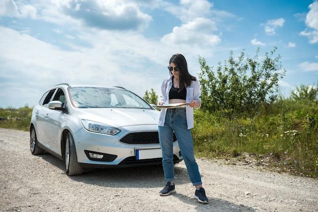 Mulher jovem se perdeu e procura um mapa para planejar nova viagem
