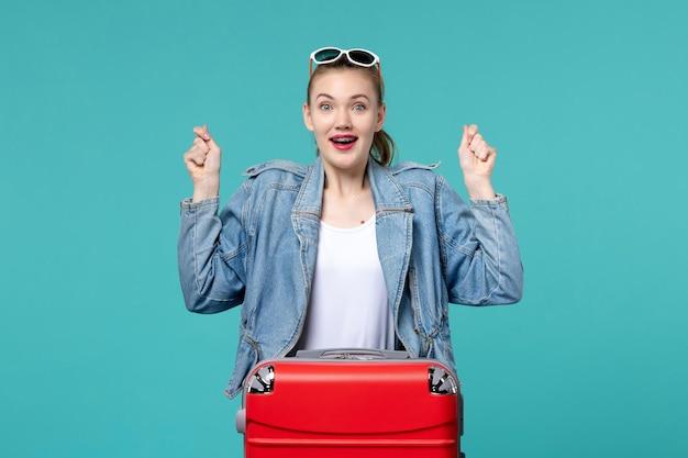 Mulher jovem se preparando para a viagem e se sentindo animada no espaço azul