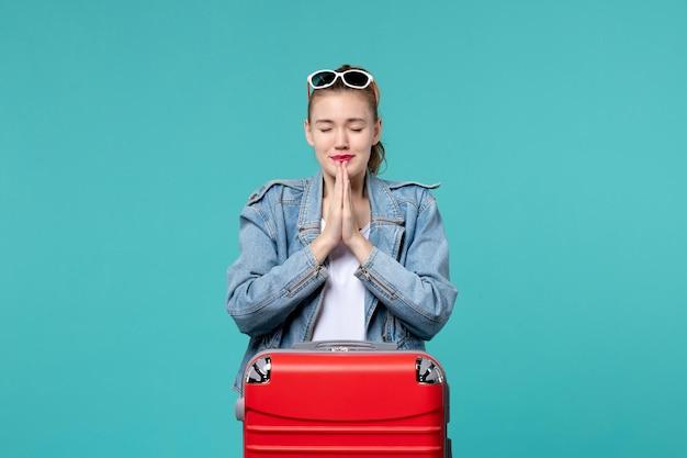 Mulher jovem se preparando para a viagem orando no espaço azul